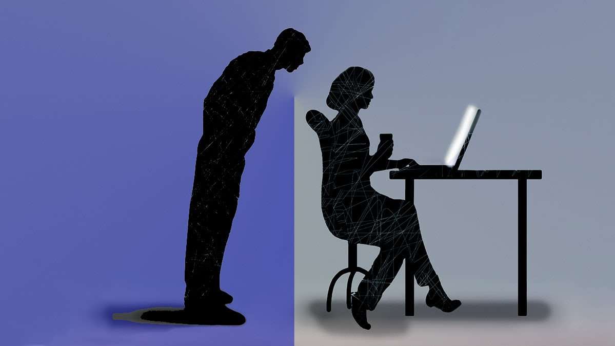 A man looking over a woman's shoulder as she works on a computer.