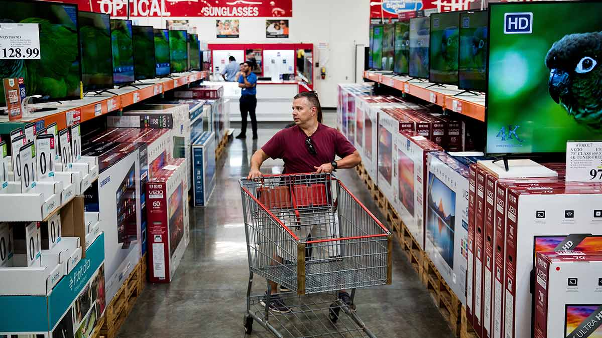 A shopper looking for TV bargains in a store.