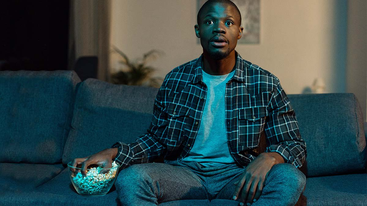 A person eating popcorn on a couch, watching a TV that's out of the picture.