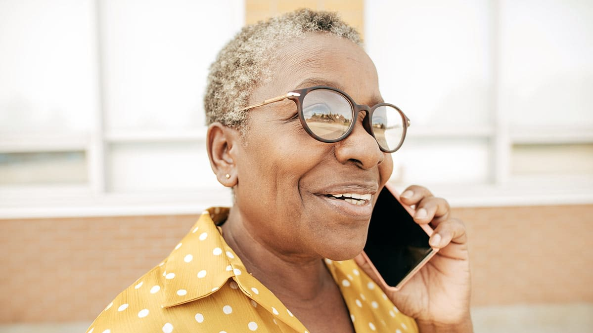 A woman holding a cell phone to her ear. The best cell-phone plans can save seniors money.