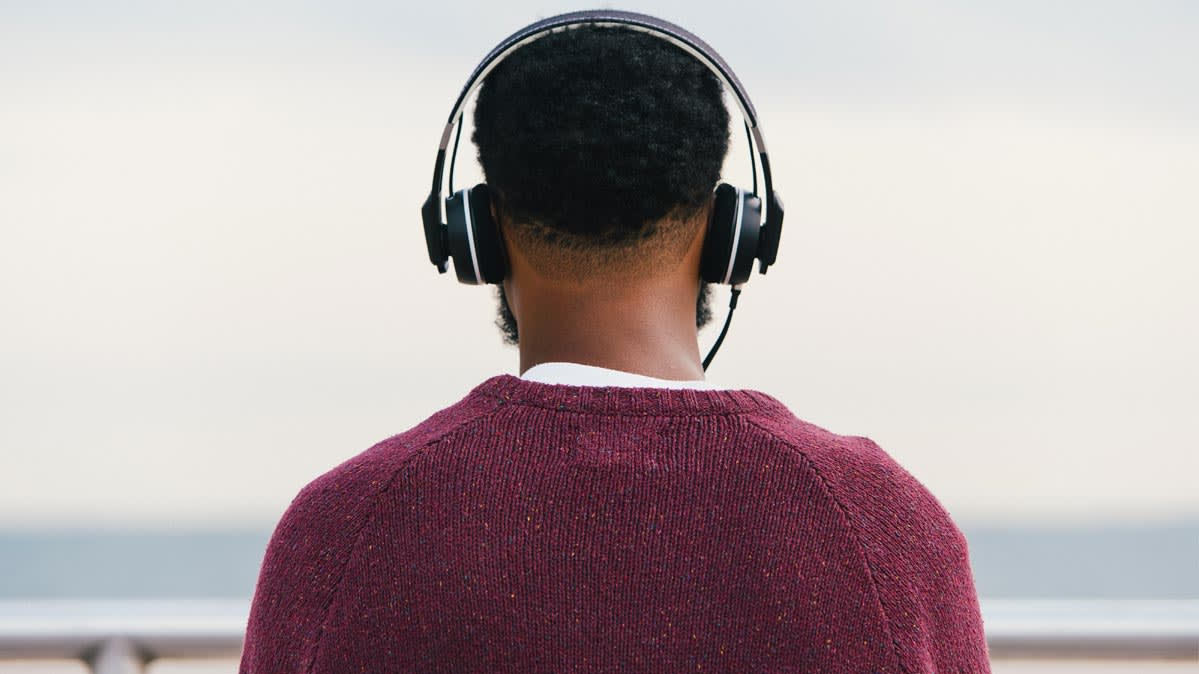 Man at beach in cool weather wearing over-ear headphones.