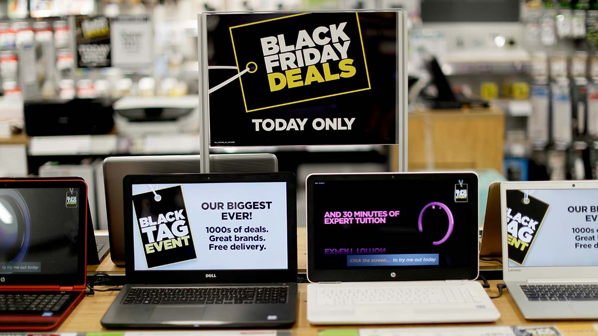 Laptop models on a store shelf beneath a Black Friday sales sign.