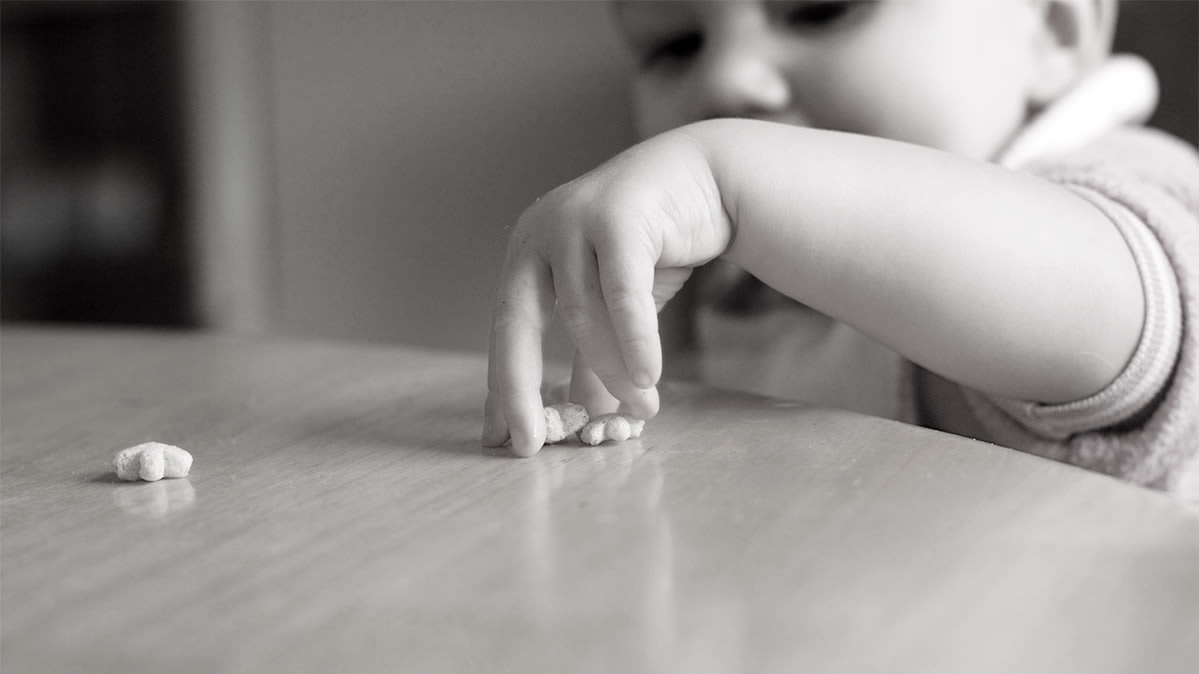 A toddler reaching for a snack food. Consumer Reports has found heavy metals in baby foods.