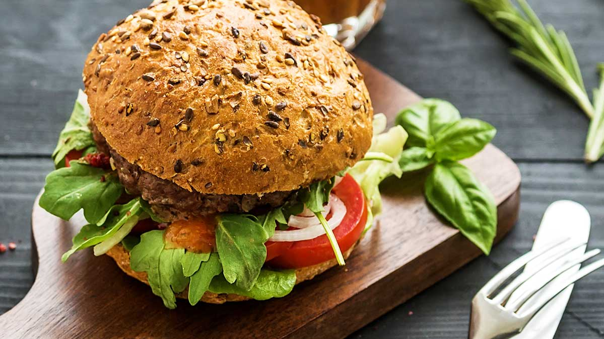 A healthy burger with a whole-wheat bun and lettuce and tomato.