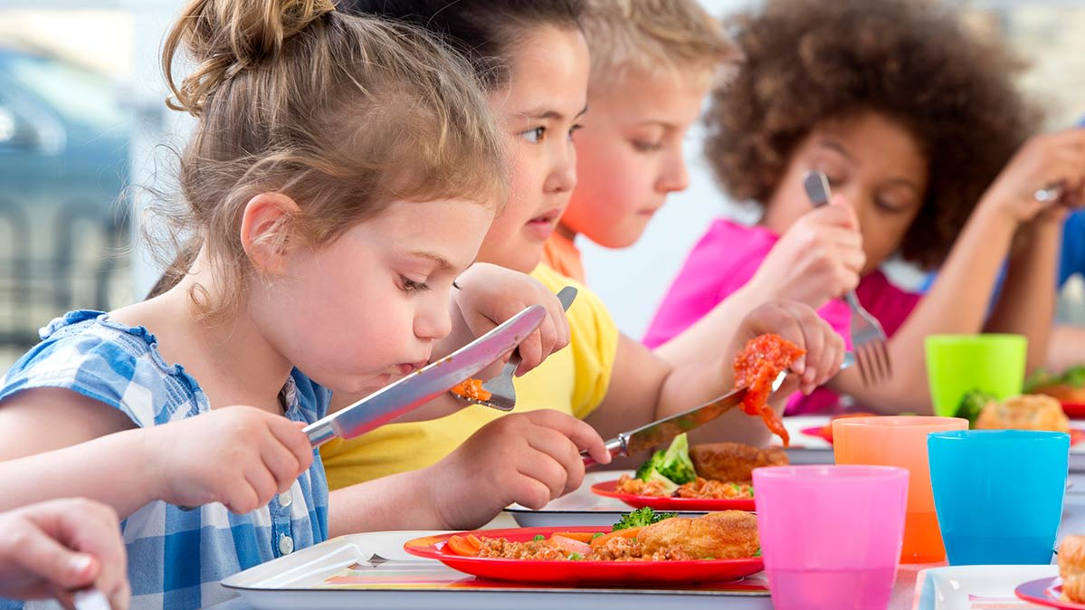 Choosing a healthy school lunch isn't always easy, but we have some tips. Pictured: children eating.