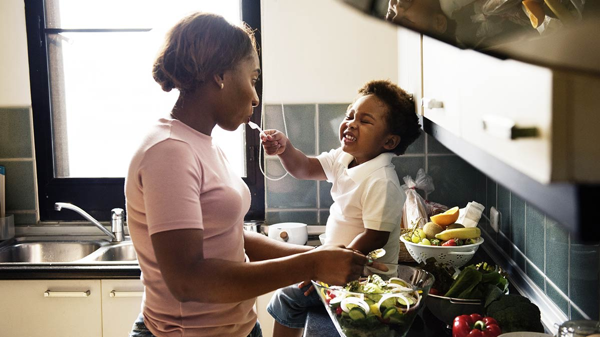 Mother cooking with her child, using healthy cooking tips.