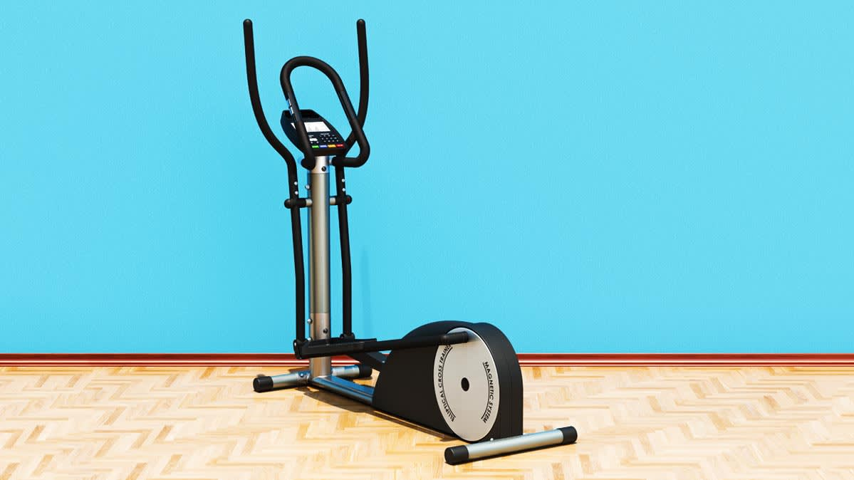 An elliptical in front of a blue wall.