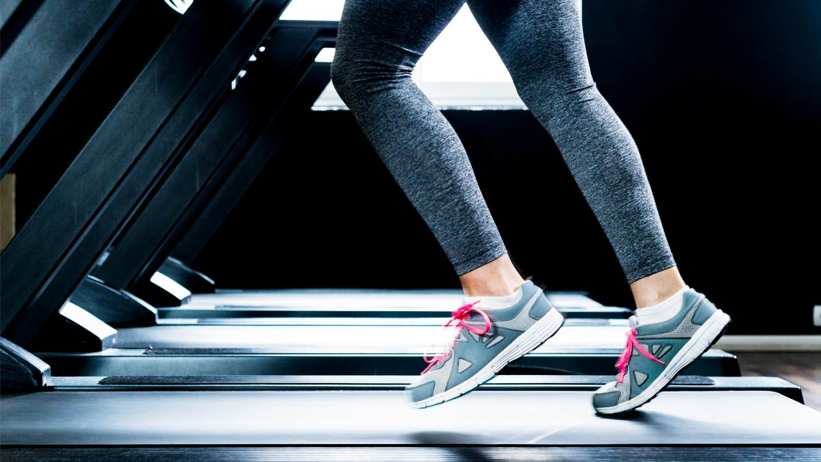 A woman in sneakers running on a treadmill.