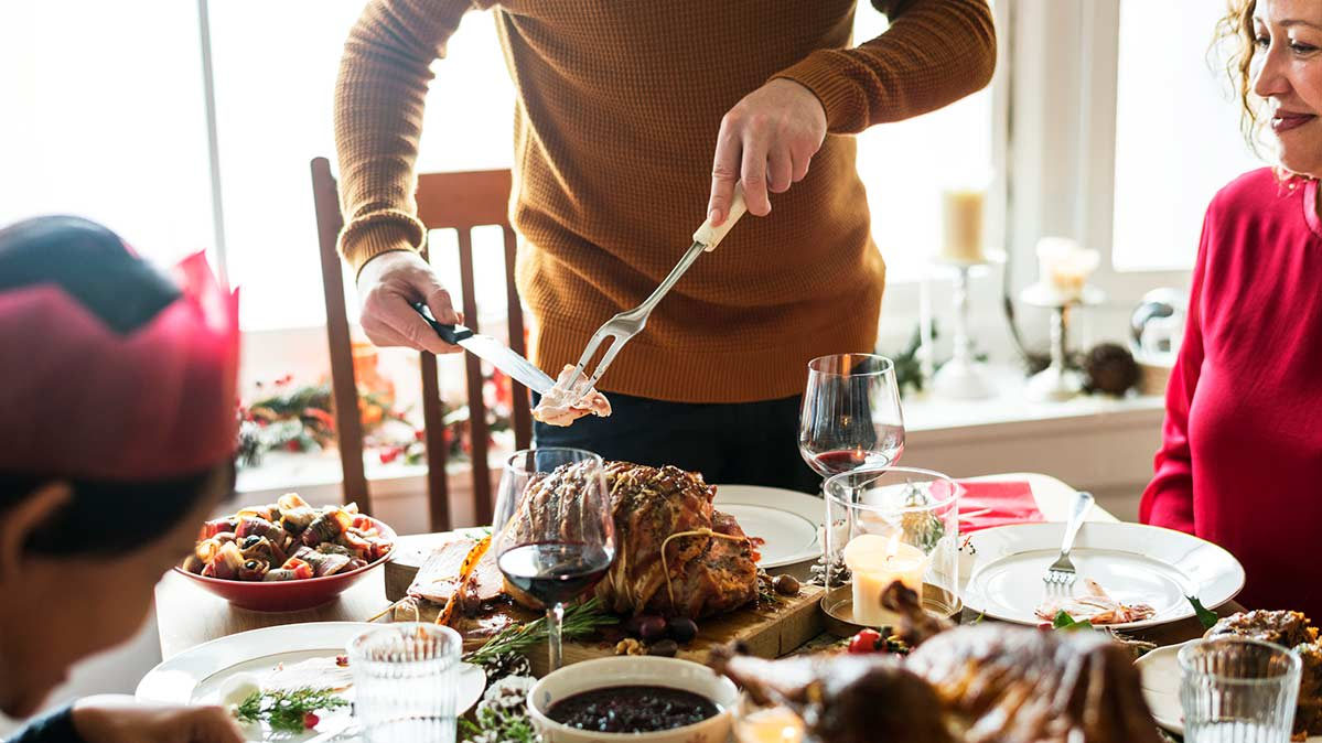 A family enjoying a holiday meal with a person carving a holiday roast