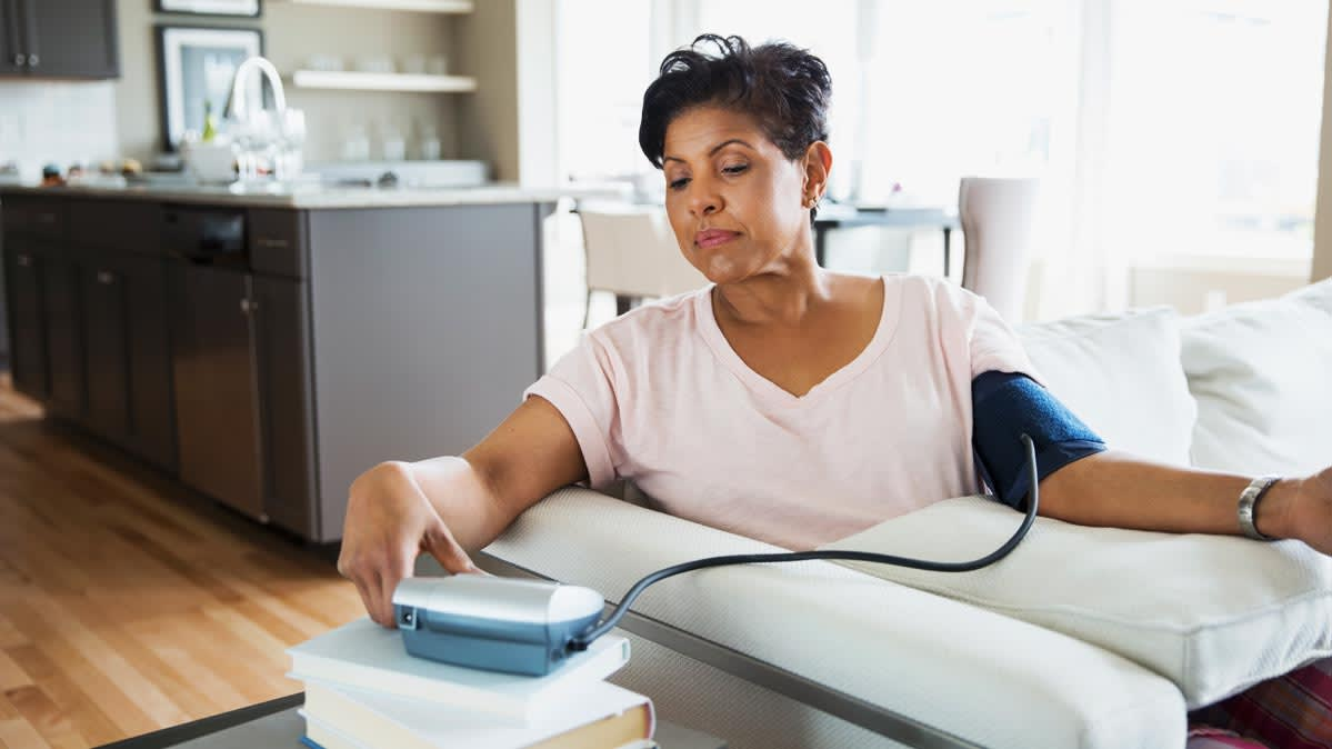 A woman checks her blood pressure using a monitor at home.