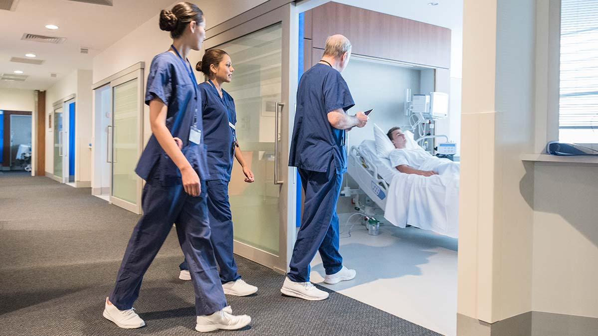A group of doctors walking into a patient's hospital room.