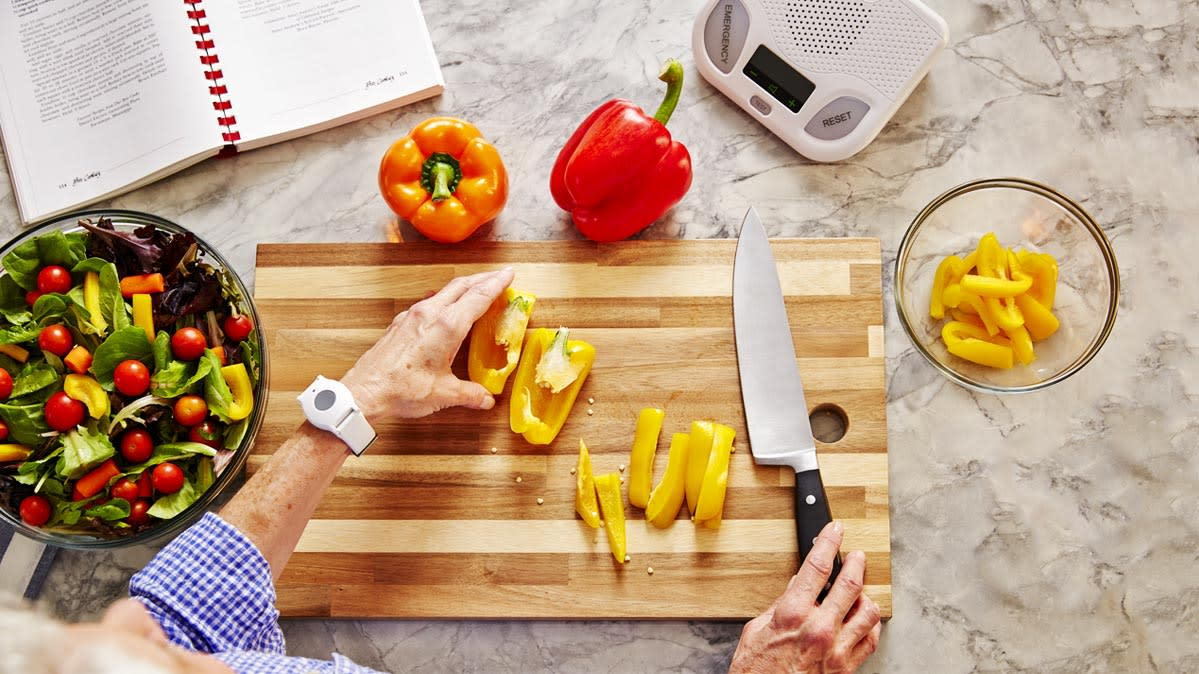 An older adult uses one of many available medical alert systems while cooking.