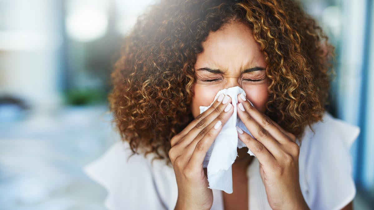 Woman sneezing in to tissue