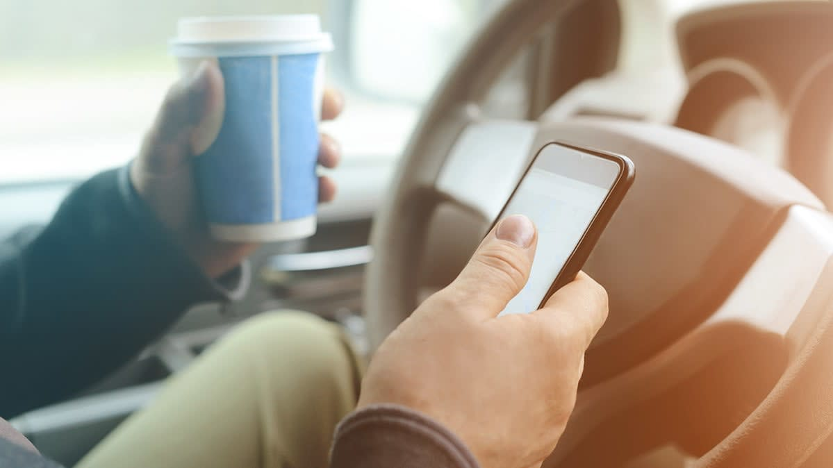 Car driver with coffee and smart phone