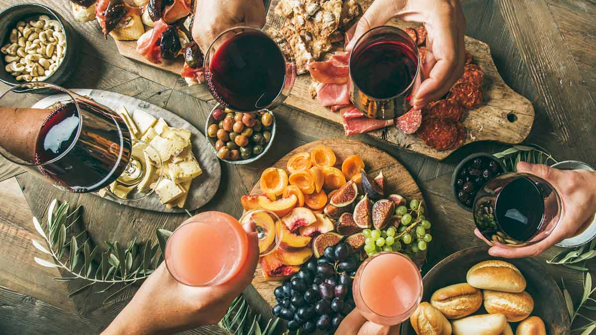 A holiday meal with fruit, meat, olives, and wine.