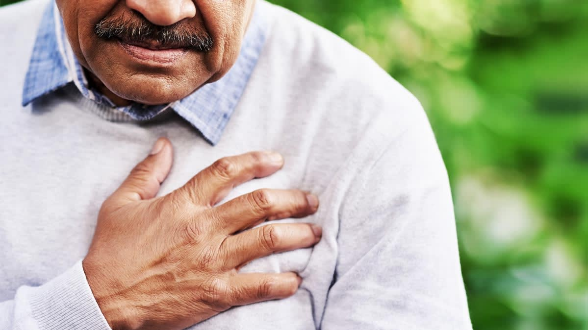 A man with heartburn clutching his chest.