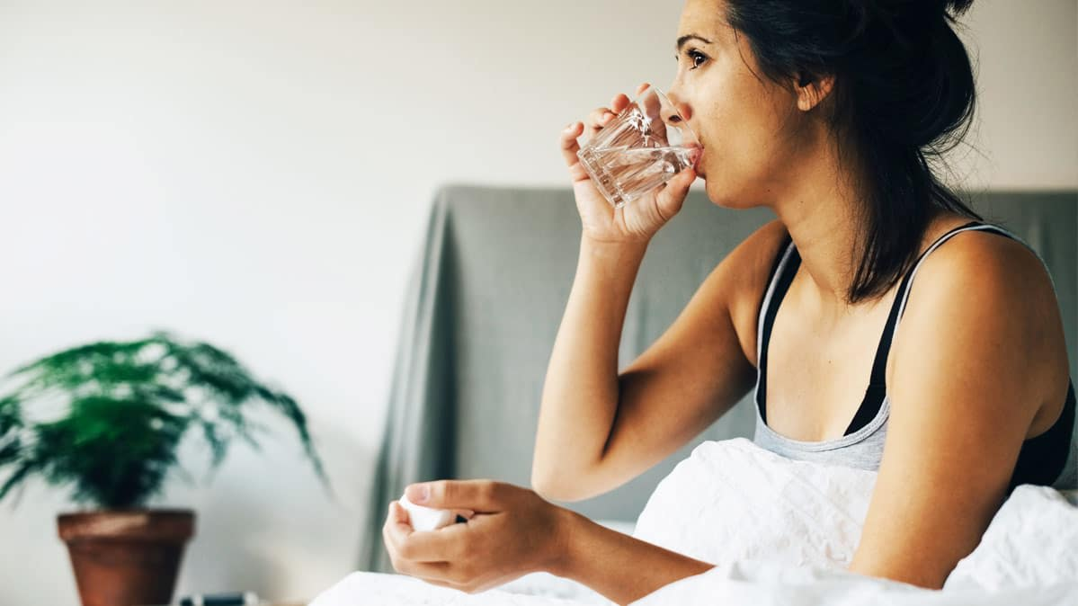 A woman drinks some water while in bed.
