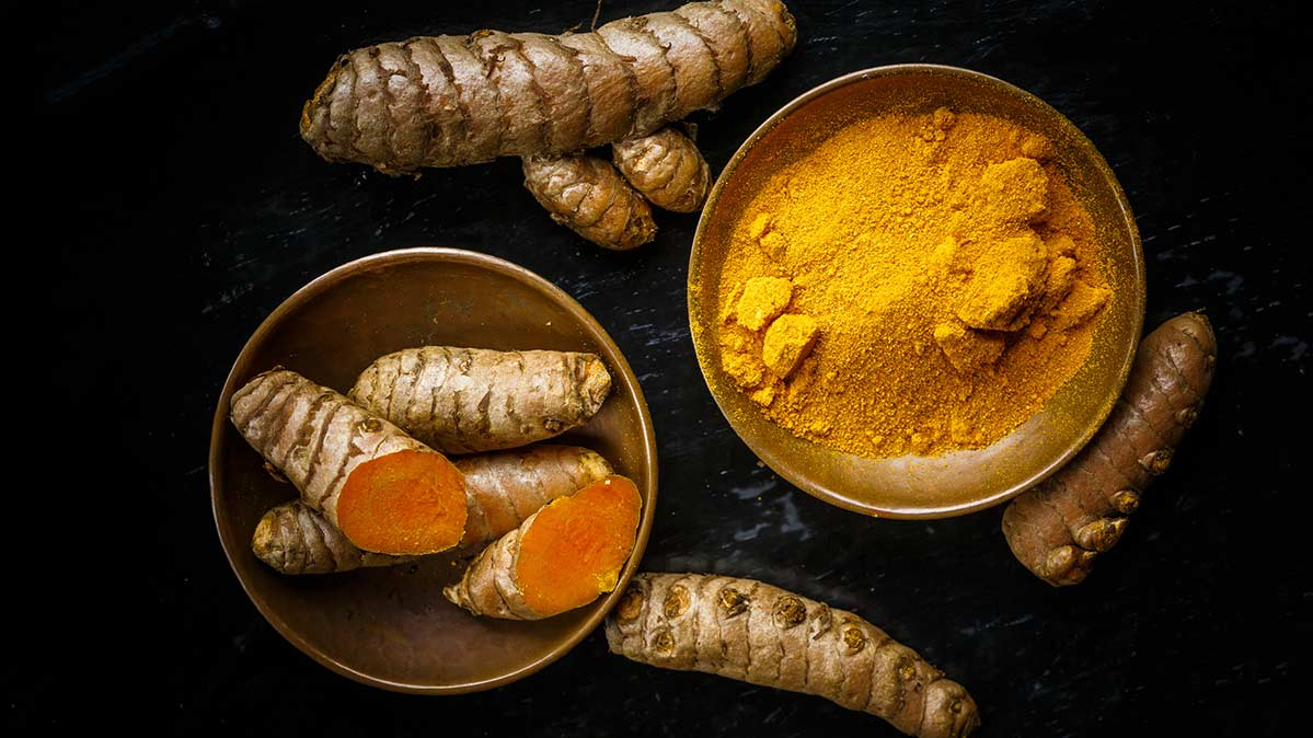 Turmeric roots in a bowl, along with another bowl of powdered turmeric.