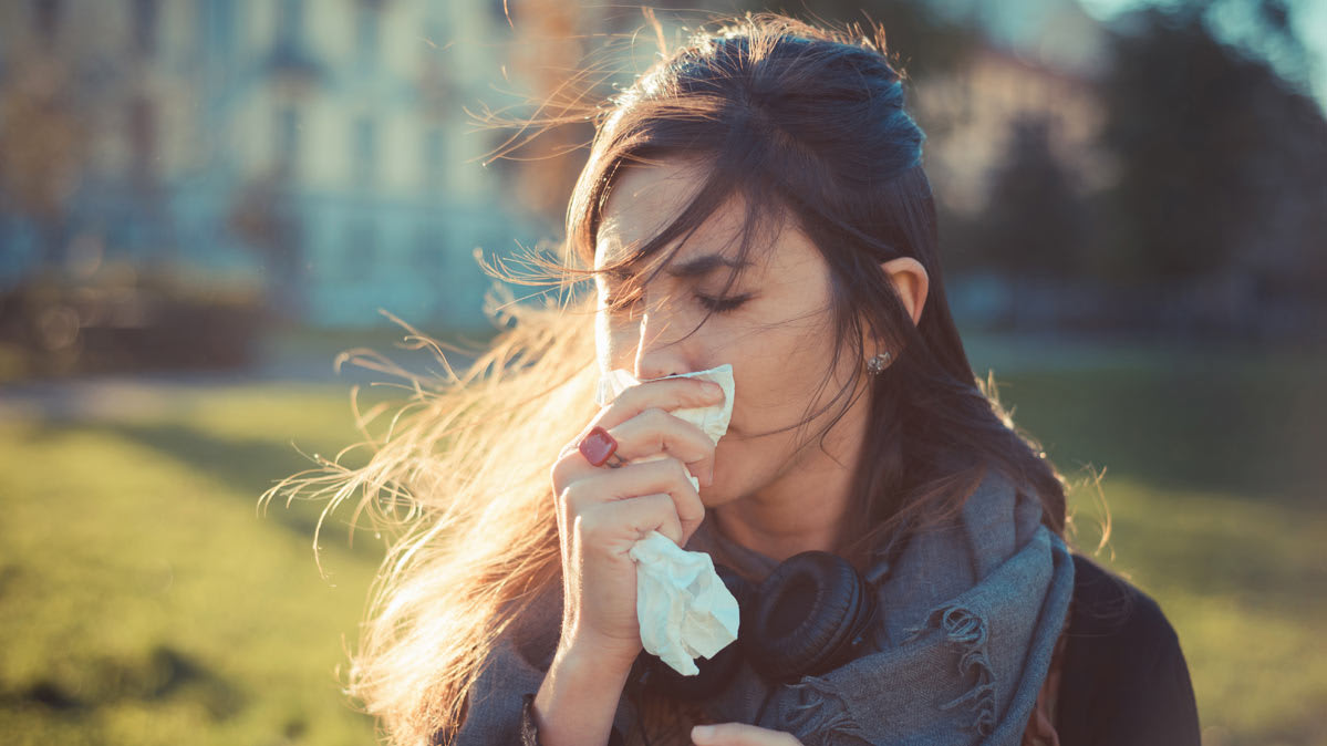 A woman holding a tissue to her nose during flu season.