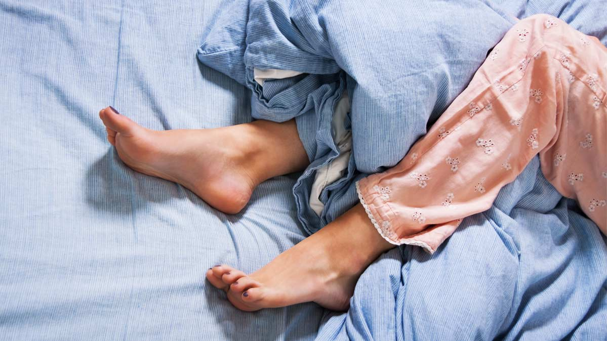 A photograph of legs in bed.