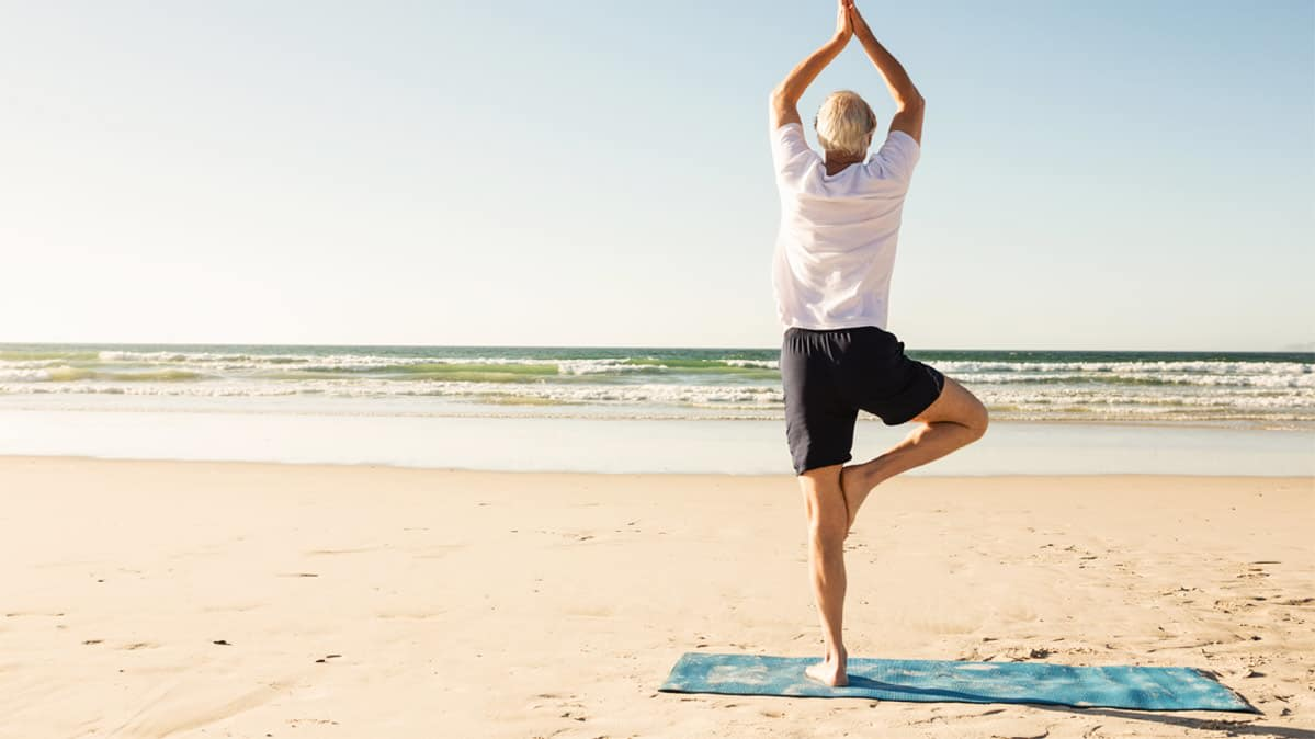 A man practices standing on one leg an the beach to improve balance.