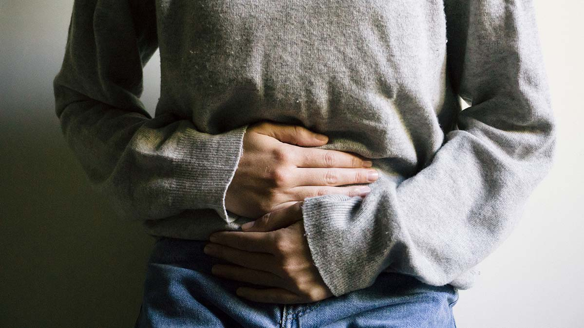 Woman holding her belly. Digestive upset is a food poisoning symptom.