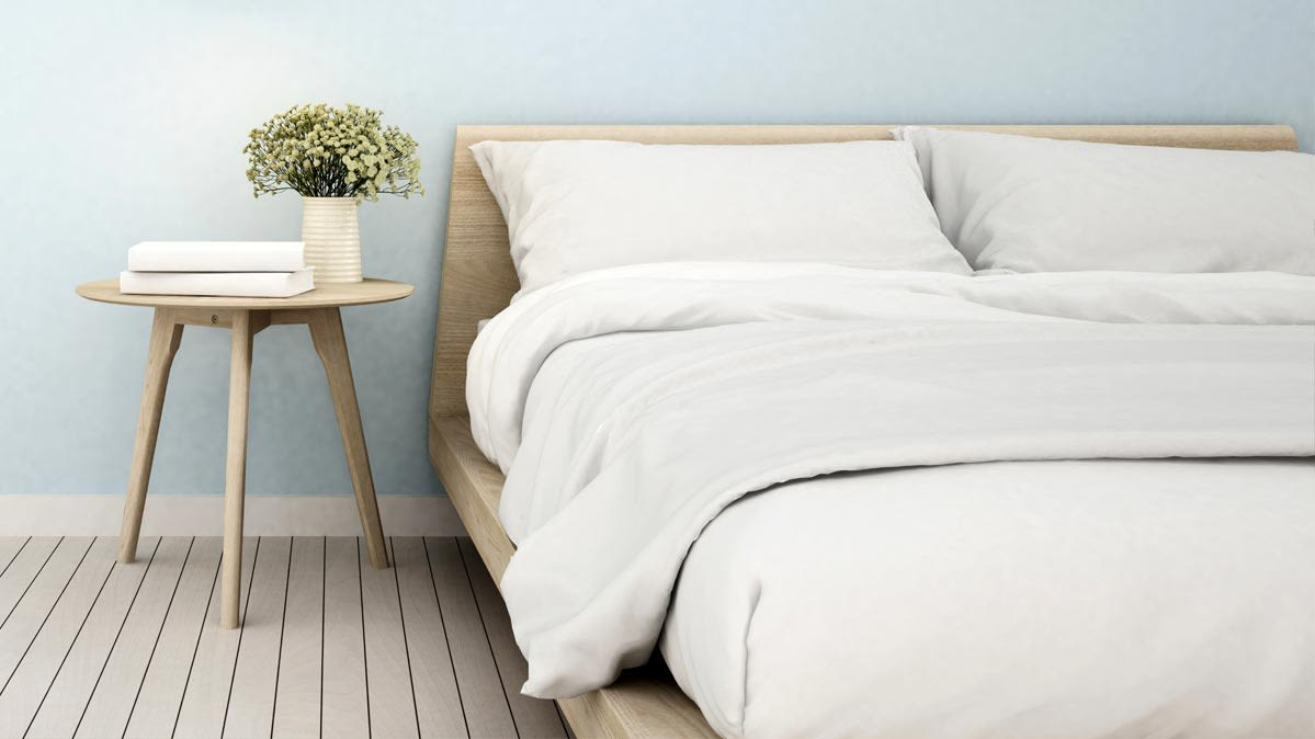A modern wooden bed made up with white bedding on the mattress
