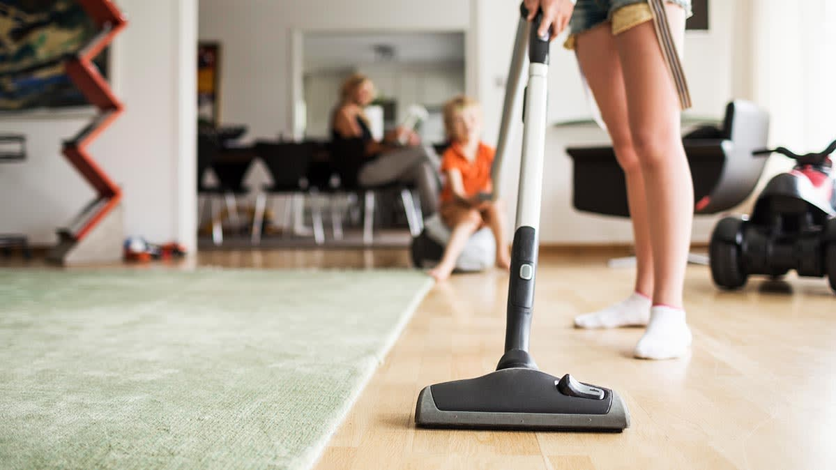 A woman vacuuming hardwood floors in a living room.