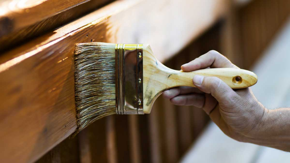 Applying a wood stain to a deck railing.