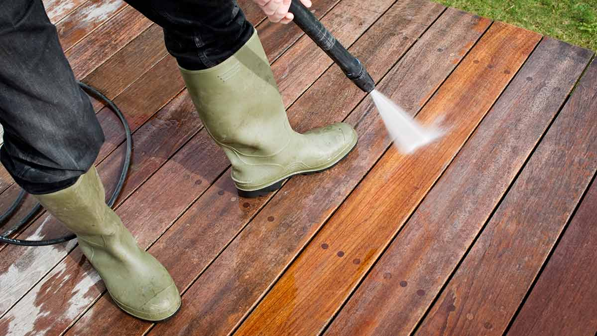A person using a pressure washer to clean a wood deck.
