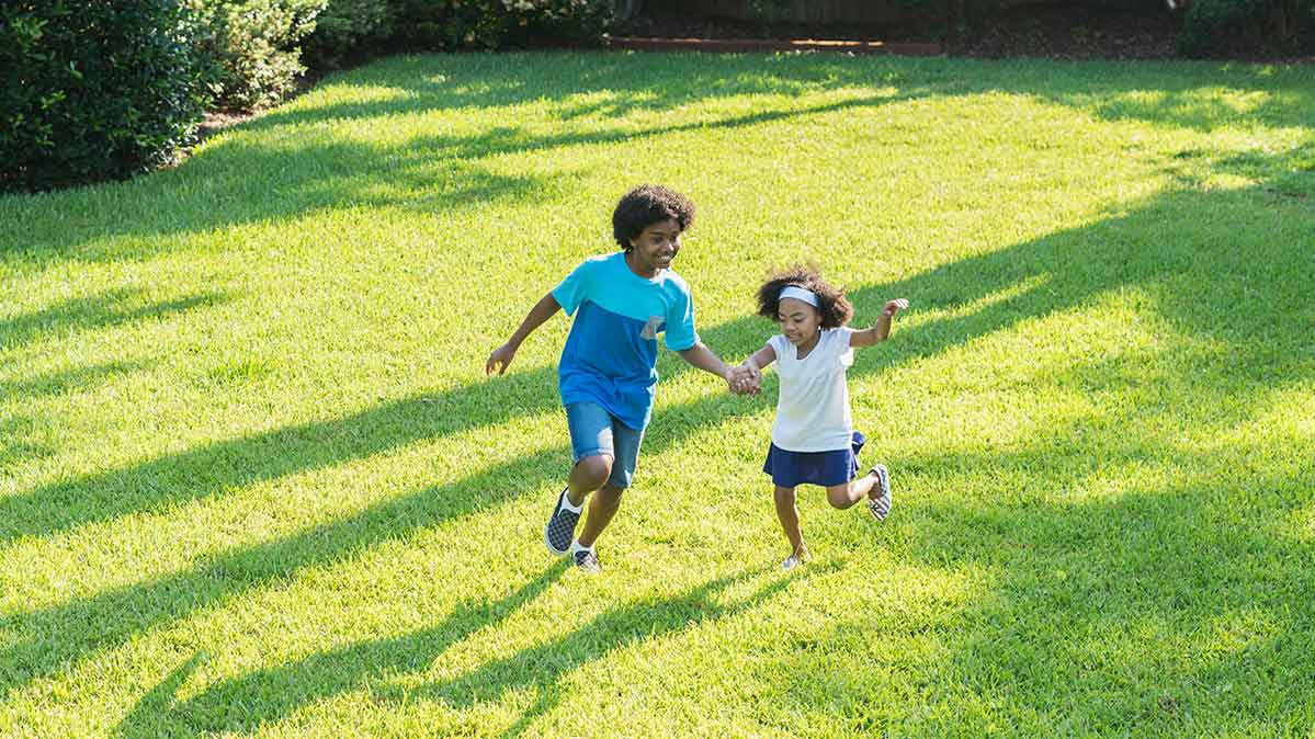 Photo of two children playing on the grass