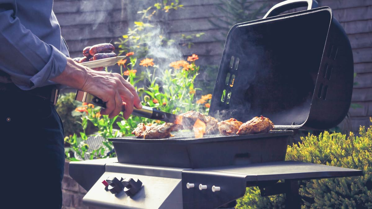 A person cooking on a gas grill in nice weather.