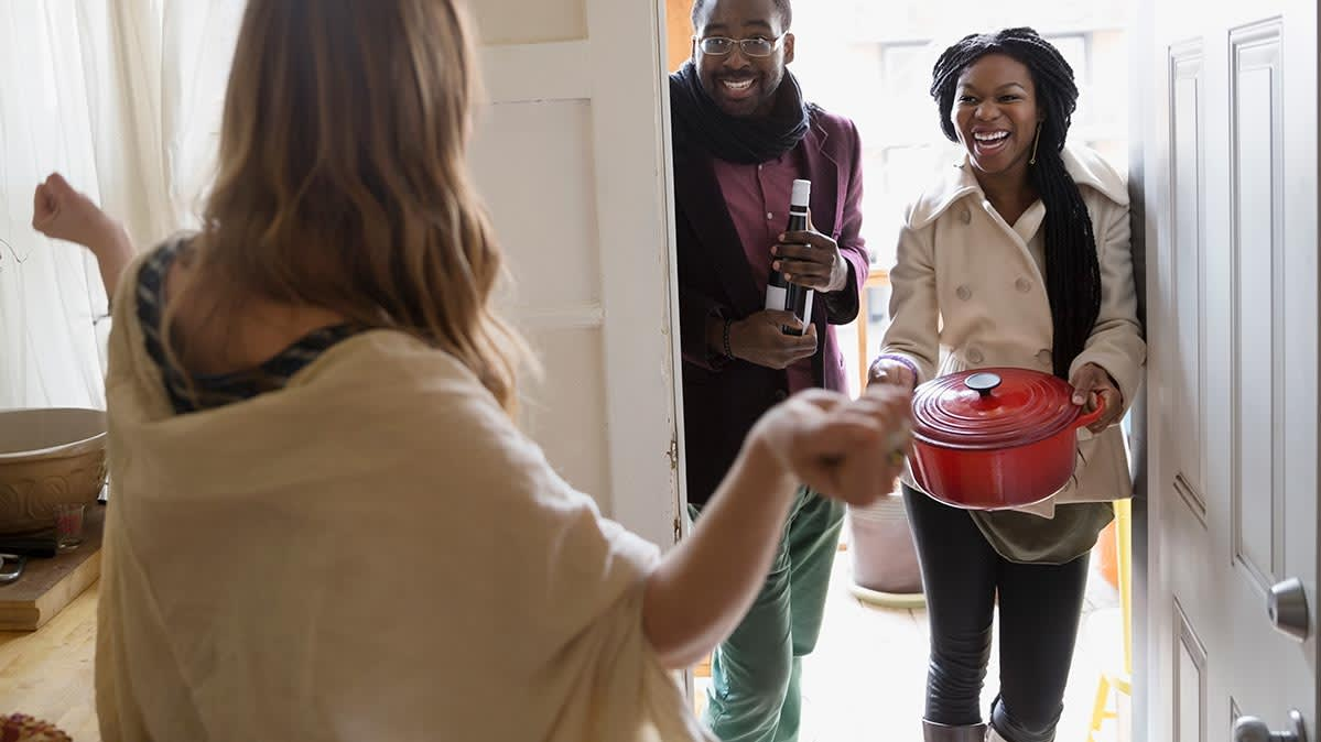 Woman welcomes two friends into her home. One is carrying a Dutch oven.