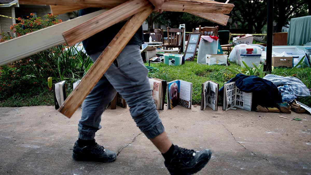 Photo of a person salvaging valuables after serious flooding, including family keepsakes strewn across a yard