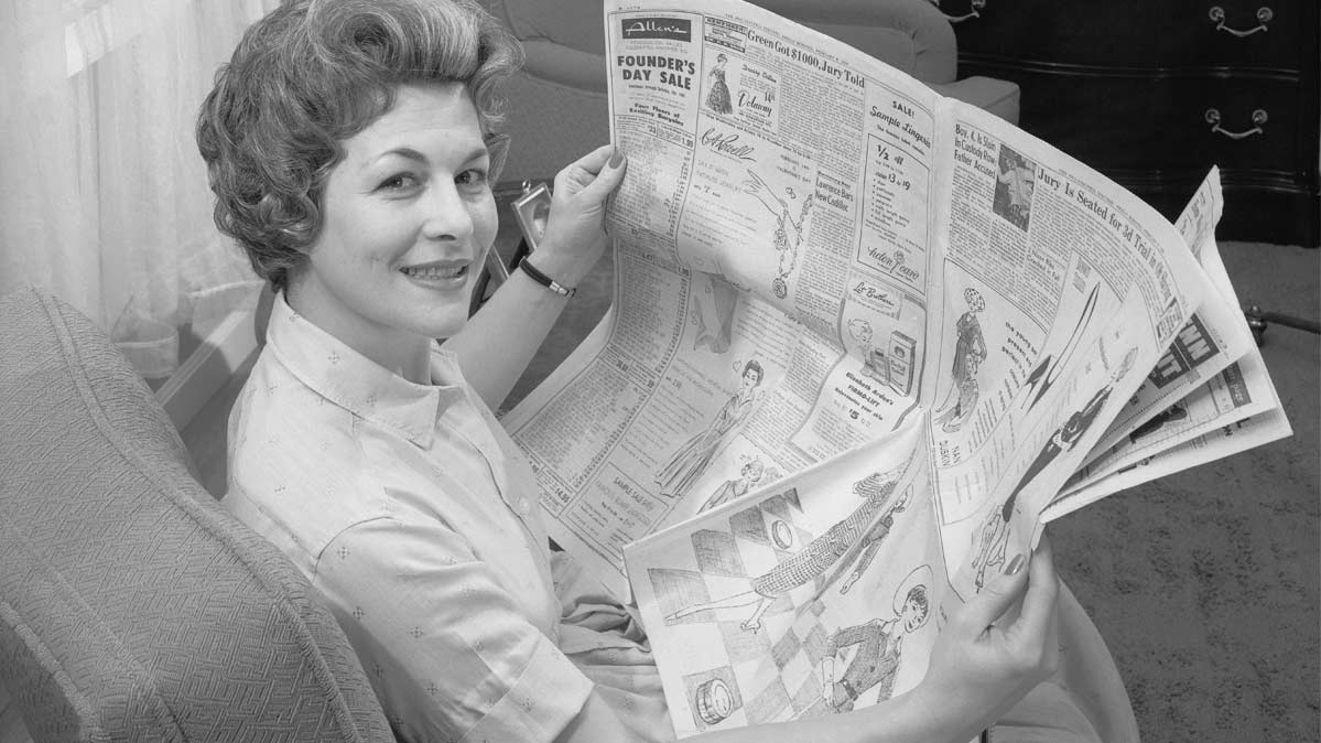 A vintage photo of a woman reading a newspaper.