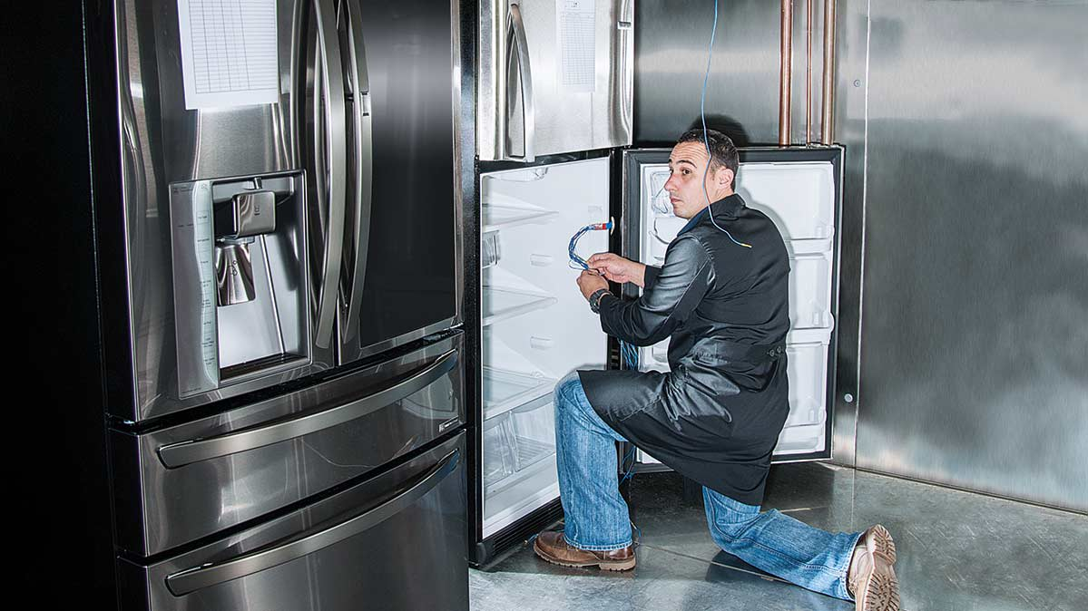 A CR engineer testing a refrigerator, one of the appliances that receives Consumer Reports' new Overall Score.