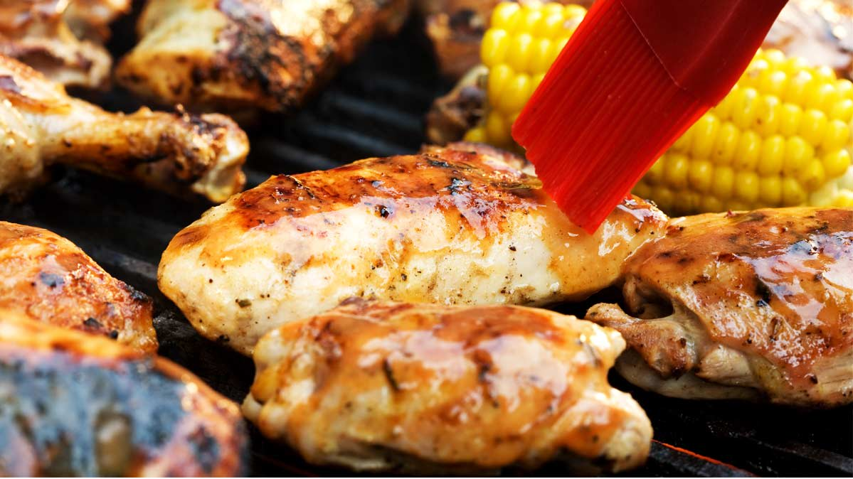 Grill equipment like this basting brush adding BBQ sauce to chicken can help you grill like a pro.