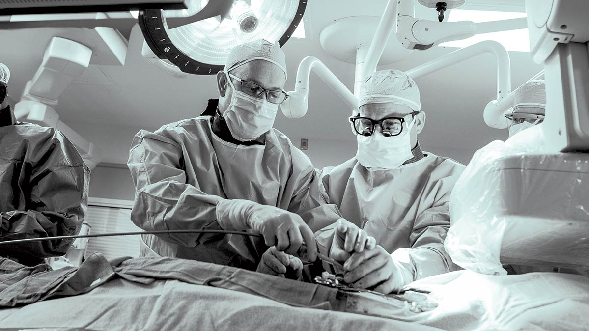 Surgeons in scrubs replace a faulty heart valve.