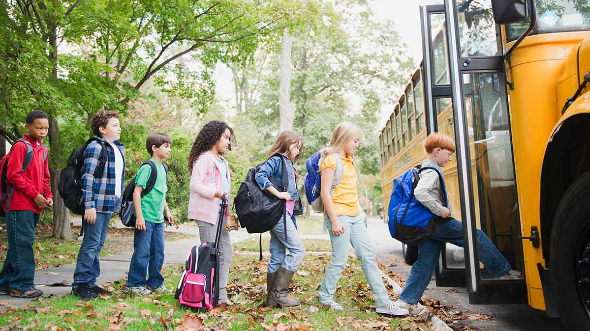 Kids getting on a school bus.