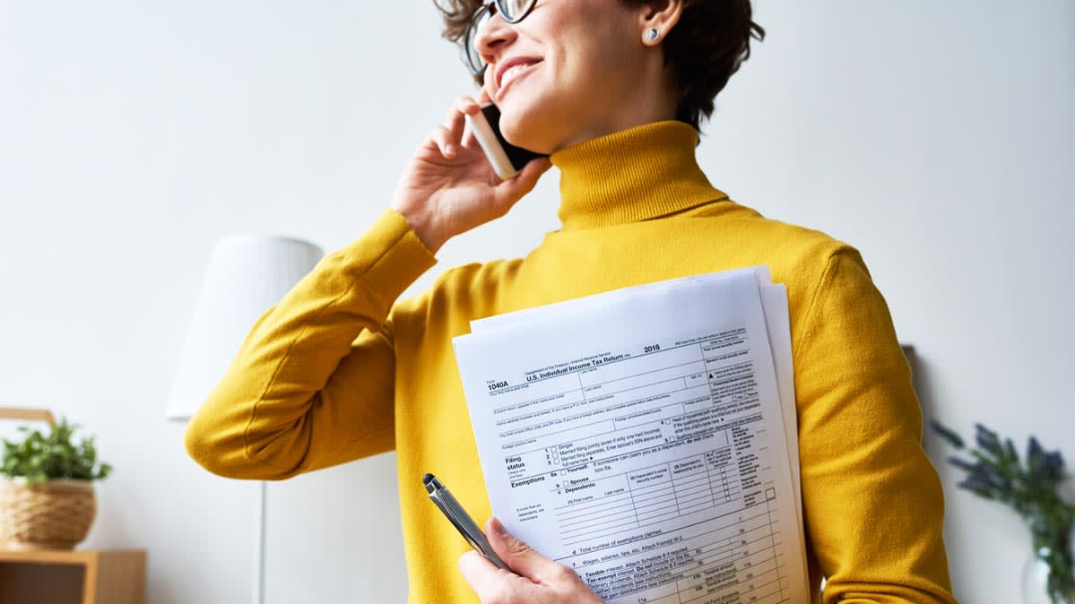 A woman in a yellow turtleneck holding tax forms.
