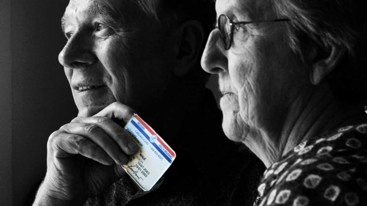 An older couple holding a Medicare card