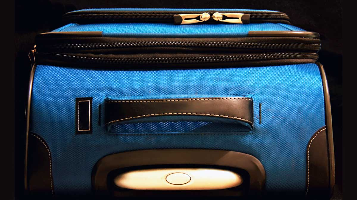 A blue carry-on piece of luggage