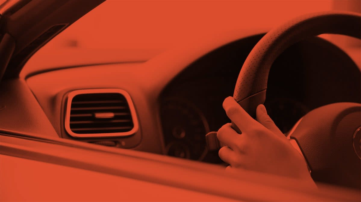 A photo of a hand on a steering wheel inside a car.