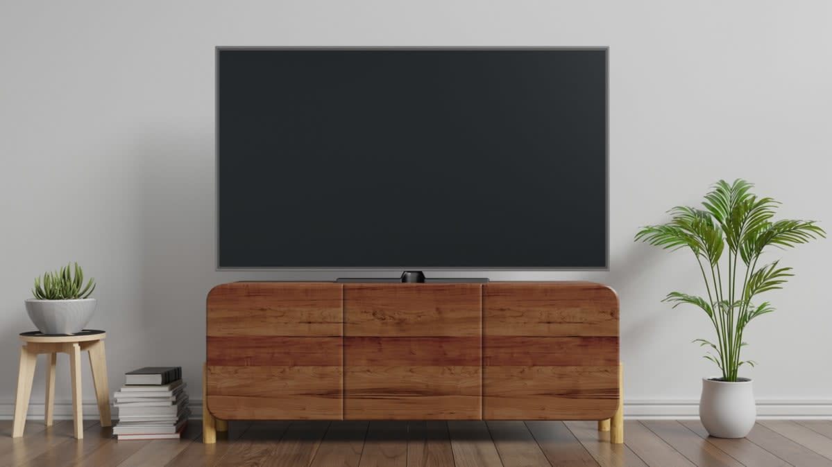 A wall-mounted TV over a wood console.