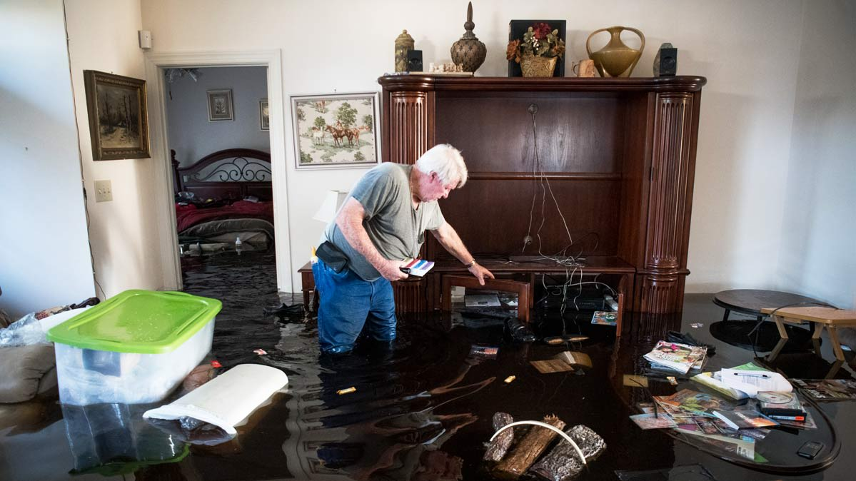 In a flooded room, a white-haired man thigh-deep in water reaches for items.