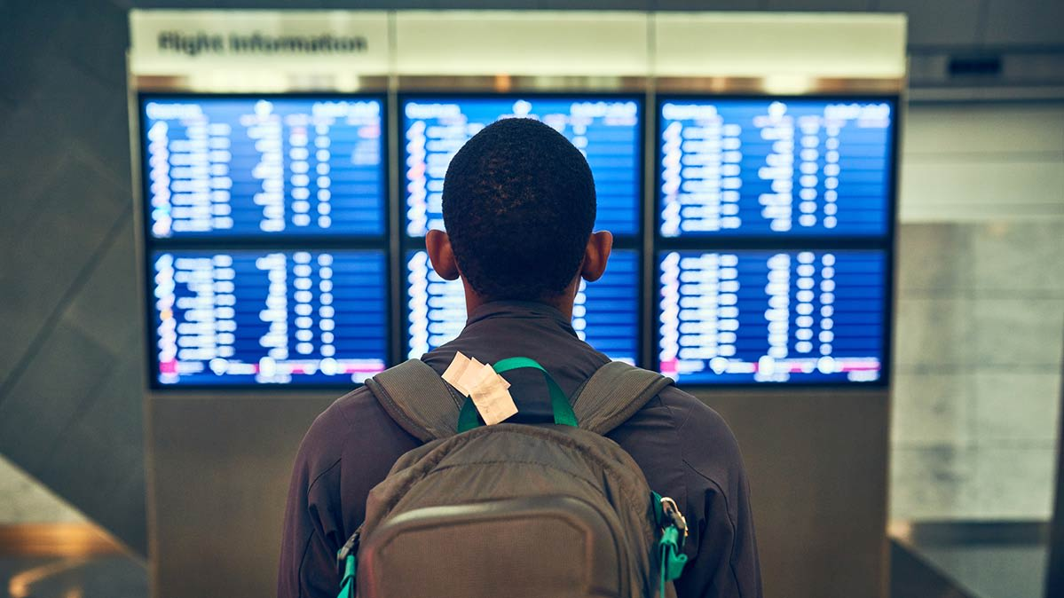 An airline passenger reviewing a departure board at the airport