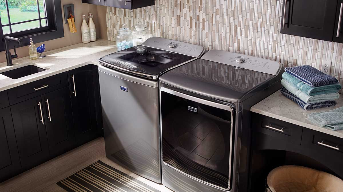 A Maytag agitator top-loader is next to a matching Maytag dryer in a laundry room.
