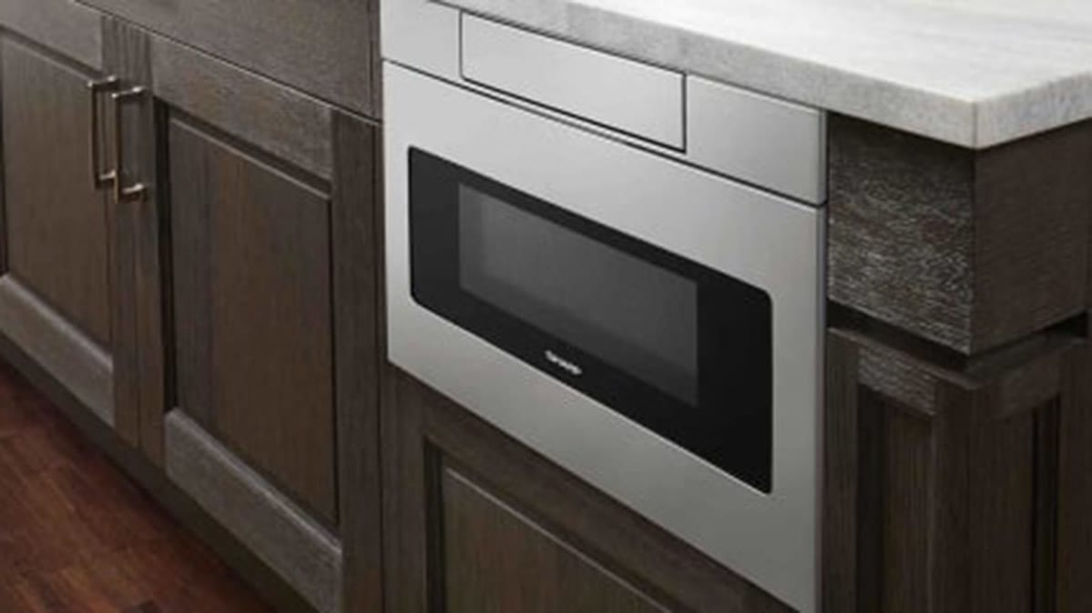 A microwave drawer sitting below a kitchen counter is a type of appliance drawer