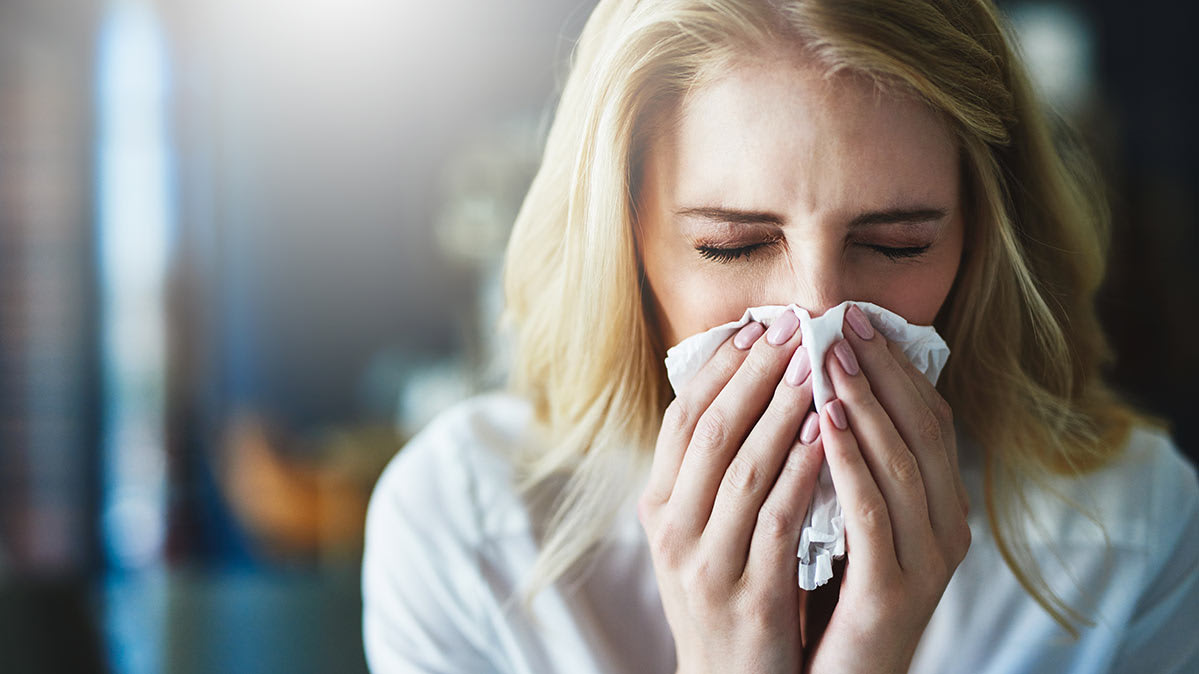 A woman with allergies sneezing.