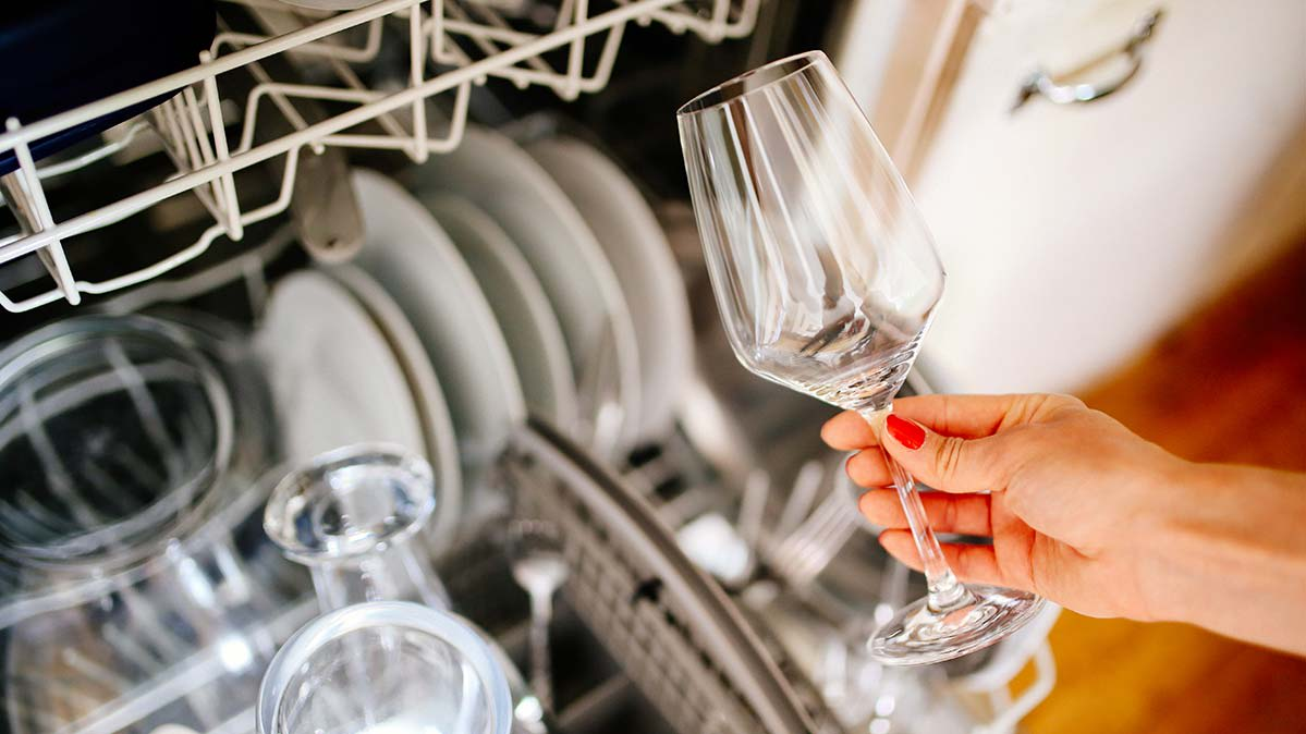 Someone taking a clean wine glass out of the dishwasher.